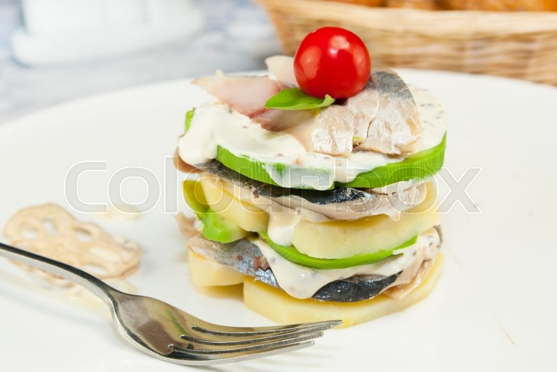 Stock image of 'Herring salad with avocado sauce on a plate in a restaurant'