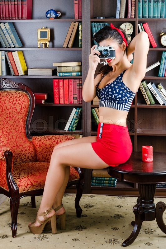 Stock image of 'Beautiful young pinup woman with retro camera posing in the library.'