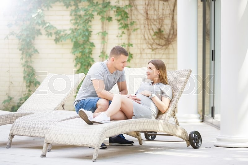 Stock image of 'Hugging young pregnant couple sitting on the deck chair in resting place'