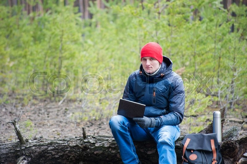 Stock image of 'a man traveling in a pine forest'