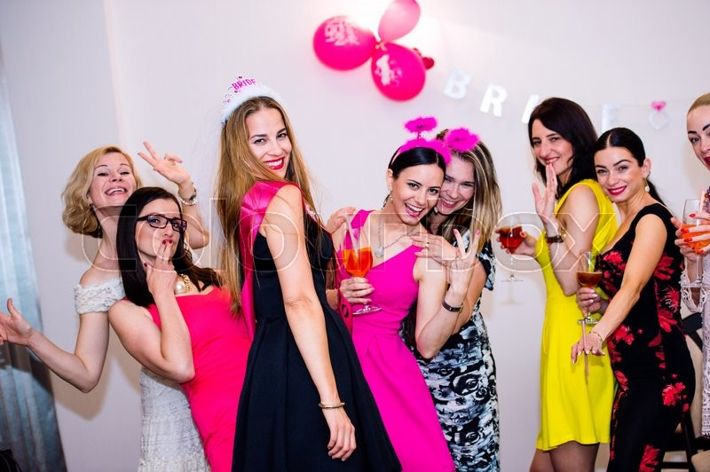 Stock image of 'Cheerful bride and happy bridesmaids celebrating hen party with drinks. Women enjoying a bachelorette party dancing.'
