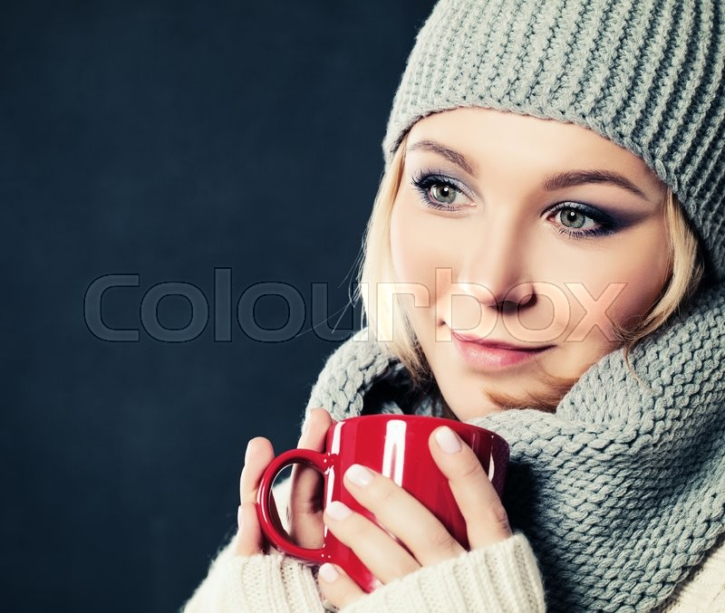 Stock image of 'Woman and Coffee or Tea Cup. Woman in Cotton Hat and Woolen Scarf on Blue Background'