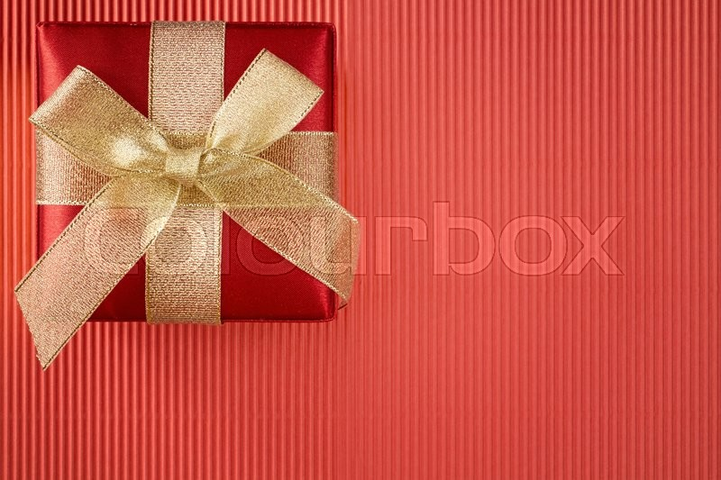 Stock image of 'Gift box on red corrugated paper background'