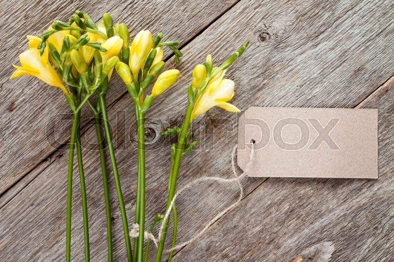 Stock image of 'Yellow freesia flowers with blank tag on old wooden background'
