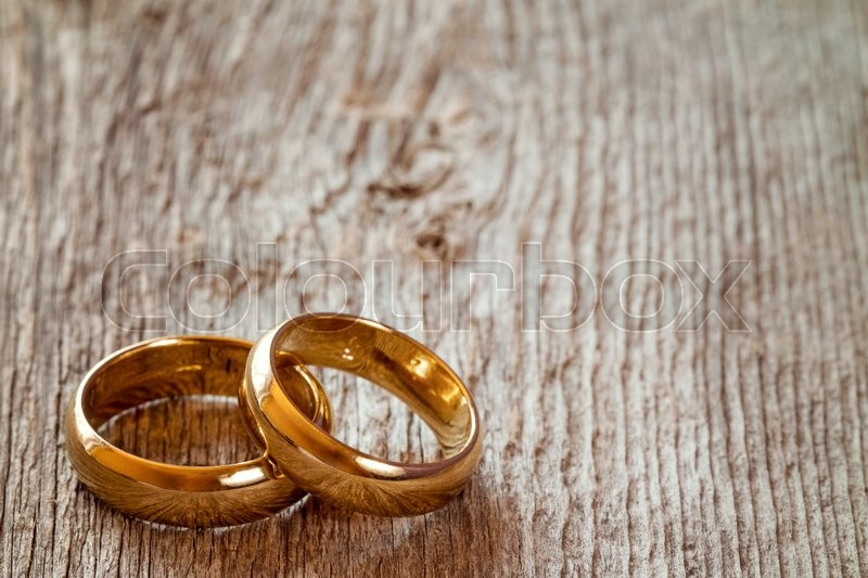 Stock image of 'Pair of golden wedding rings on wooden background'
