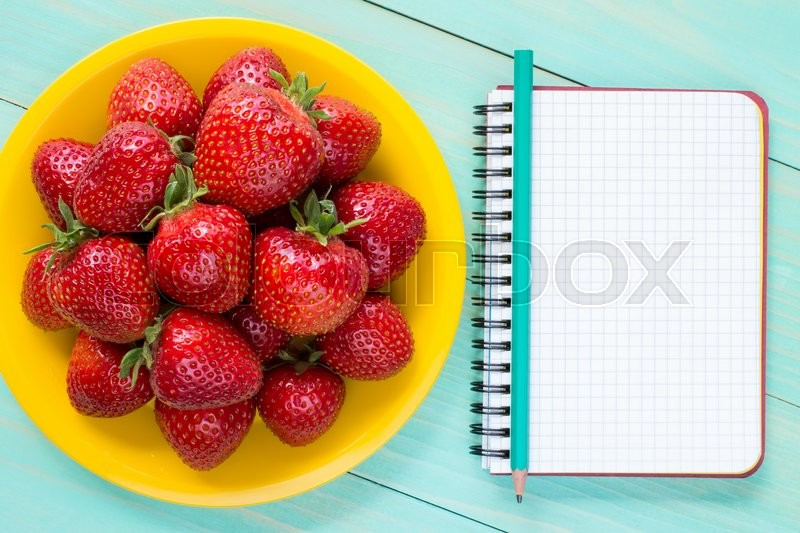 Stock image of 'Yellow plate with strawberries and blank notebook with pencil'