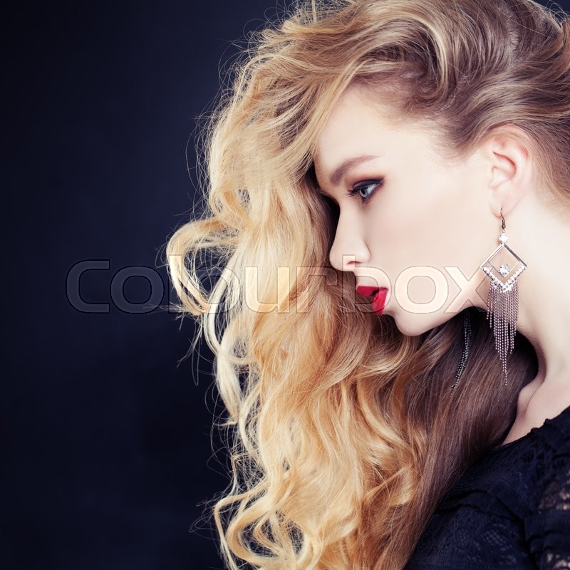 Stock image of 'Female Profile. Beautiful Woman with Long Wavy Blonde Hair on Dark Background'