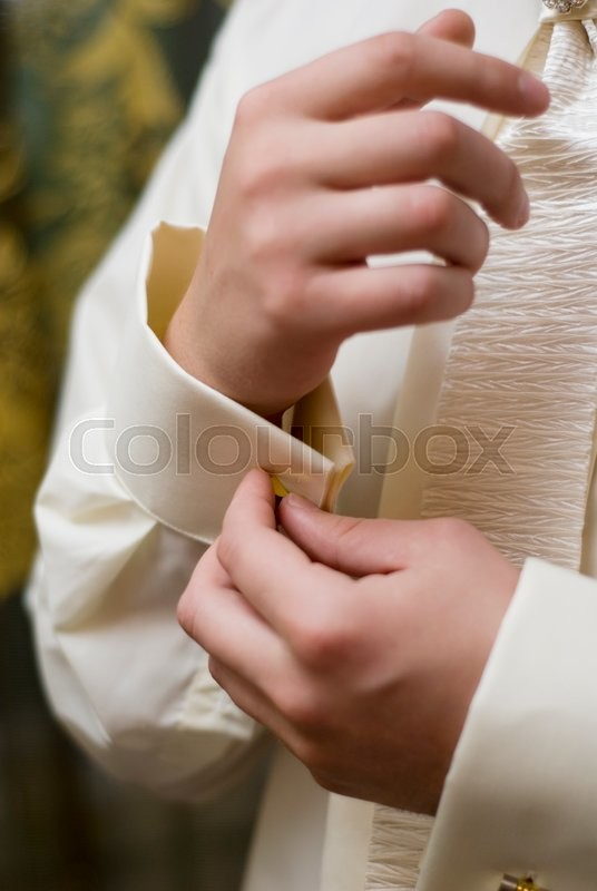 Stock image of 'the man buttoning shirt cuff on'