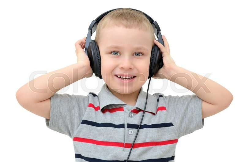 Stock image of 'Little boy listening to headphones on a white background'