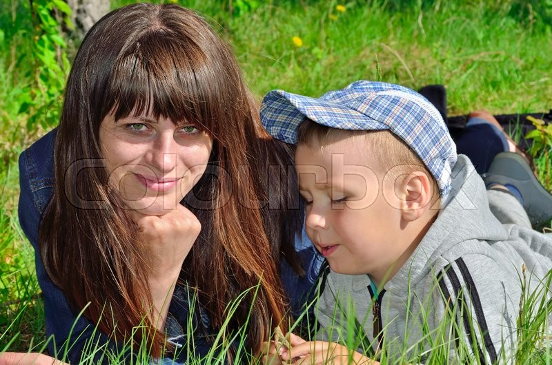 Stock image of 'Woman and child playing on green grass'