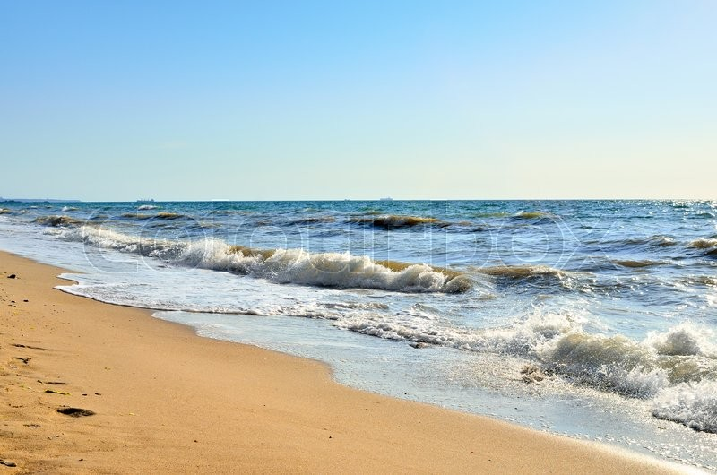 Stock image of 'Sea waves wash the beach against a blue sky'