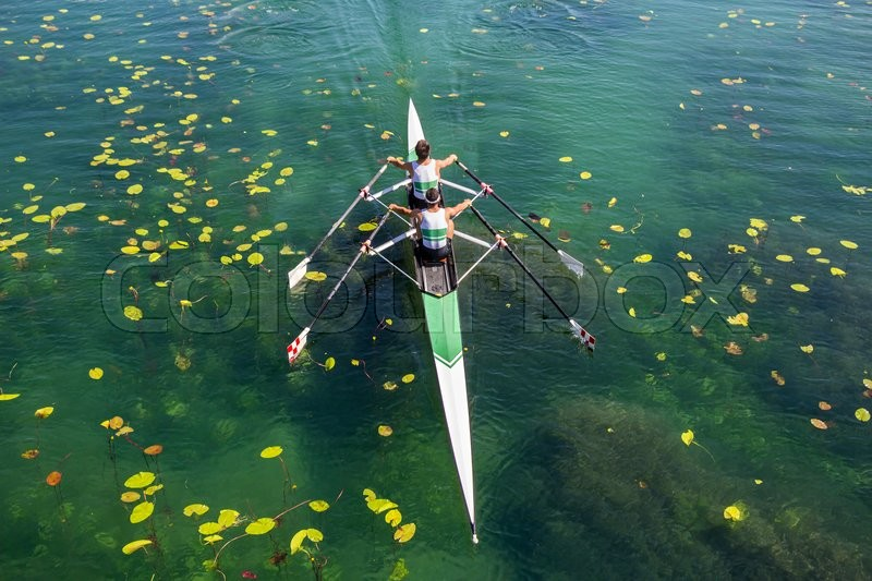 Stock image of 'Two rowers in a boat, rowing on the tranquil lake '