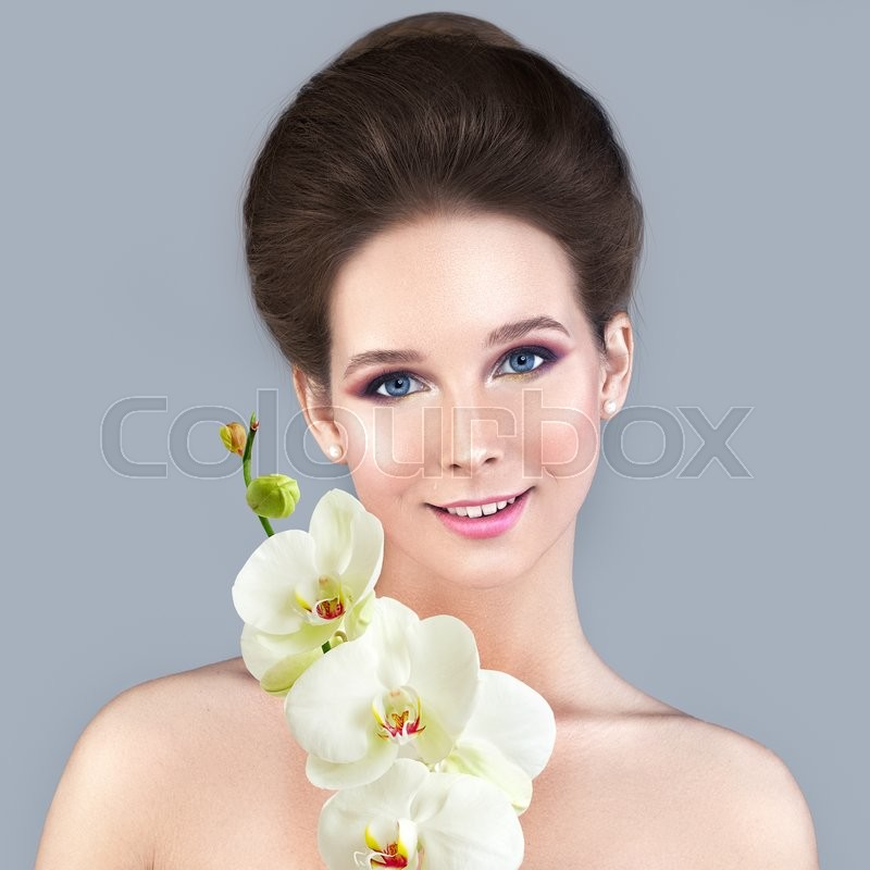 Stock image of 'Spa Skin Care Concept. Healthy Woman with Clear Skin and White Orchid Flower'