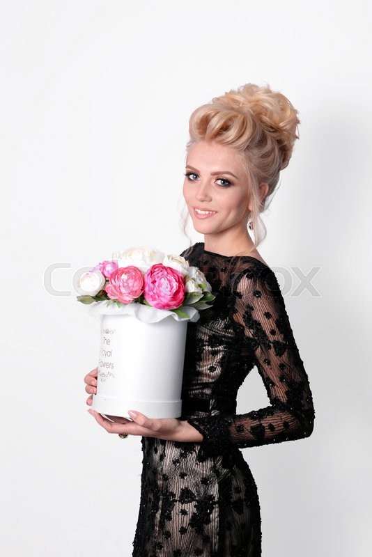 Stock image of 'Beautiful lady in elegant black evening dress with updo hairstyle and flowers in a box in her hands. Fashion photo'