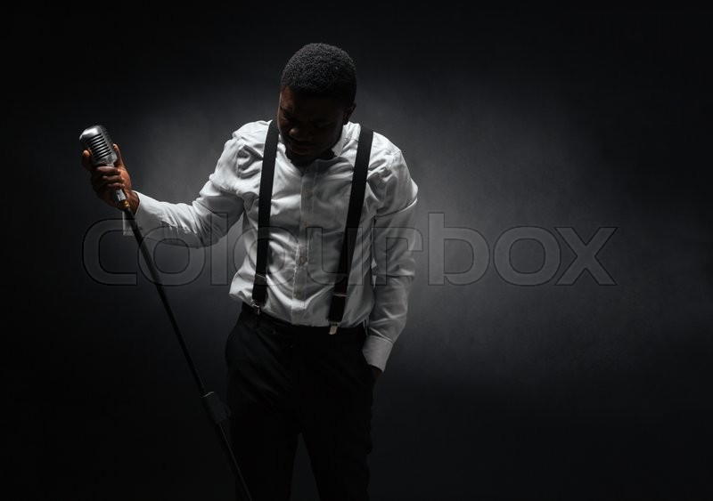 Stock image of 'Portrait of afro american male singer posing over dark background'