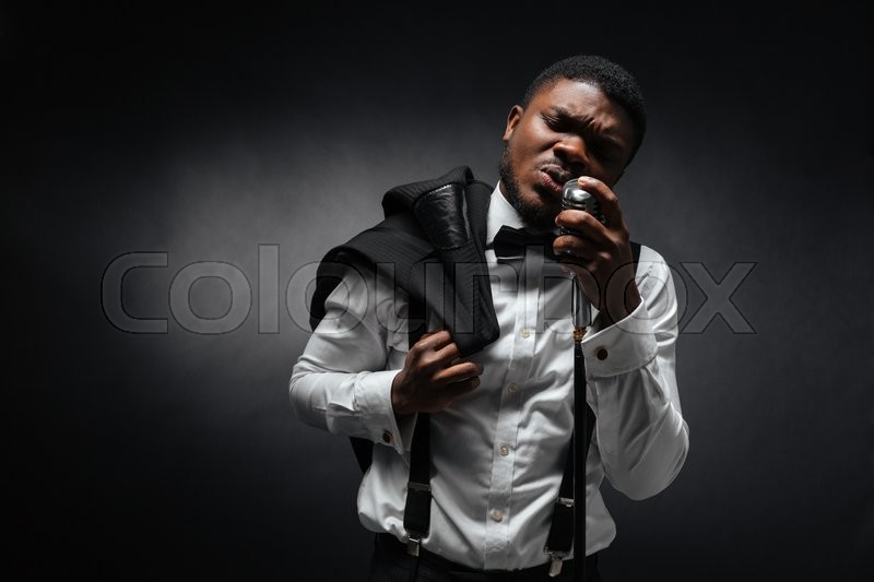 Stock image of 'Afro amerian man singing into vintage microphone over dark background'