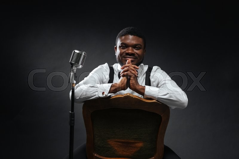 Stock image of 'Handsome afro american male singer sitting on the chair over dark background and looking at camera'