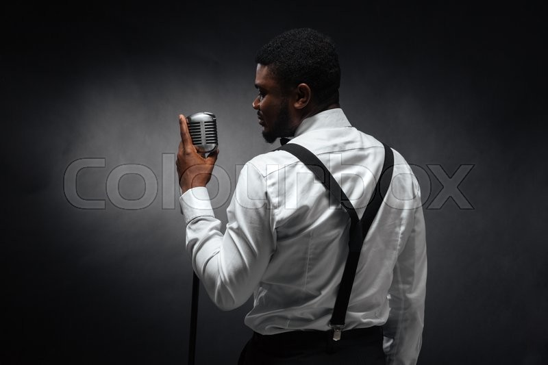 Stock image of 'Back view portrait of afro american man singing into vintage microphone over dark background'