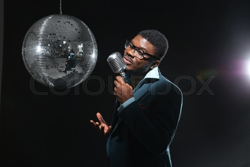 Stock image of 'Handsome afro amerian man singing into vintage microphone over dark background'
