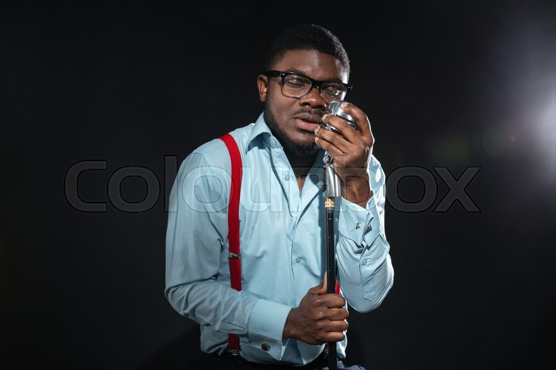 Stock image of 'Stylish afro amerian man singing into vintage microphone over dark background'