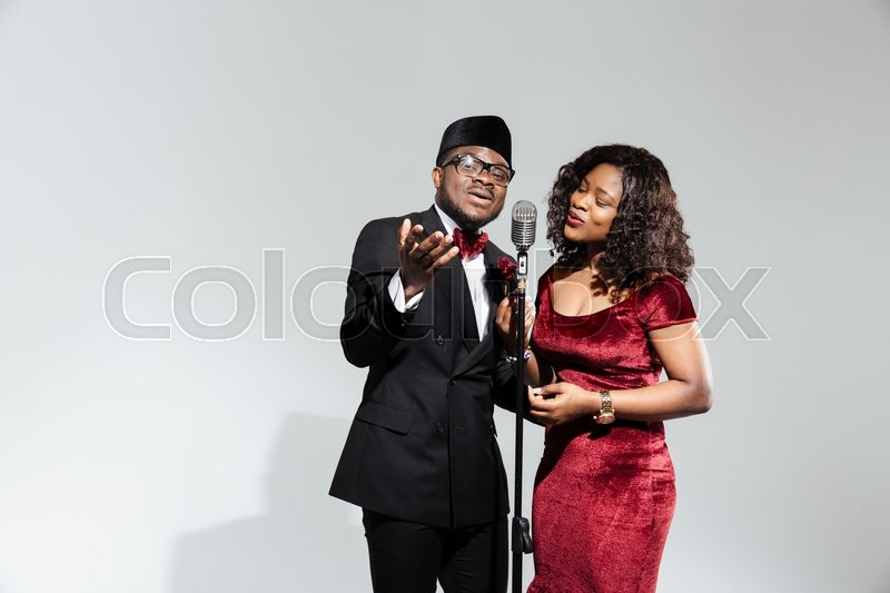 Stock image of 'Beautiful afro amerian couple singing into vintage microphone over dark background'