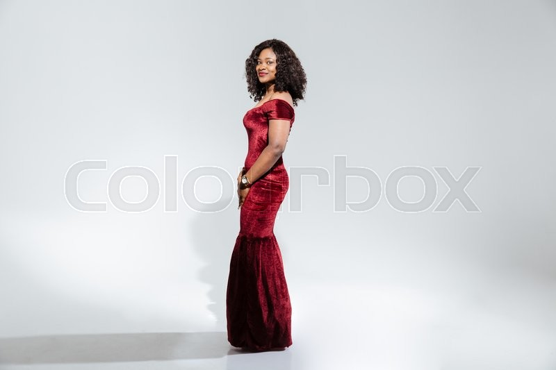 Stock image of 'Full length portrait of a beautiful afro american woman in fashion dress looking at camera isolated on a white background'