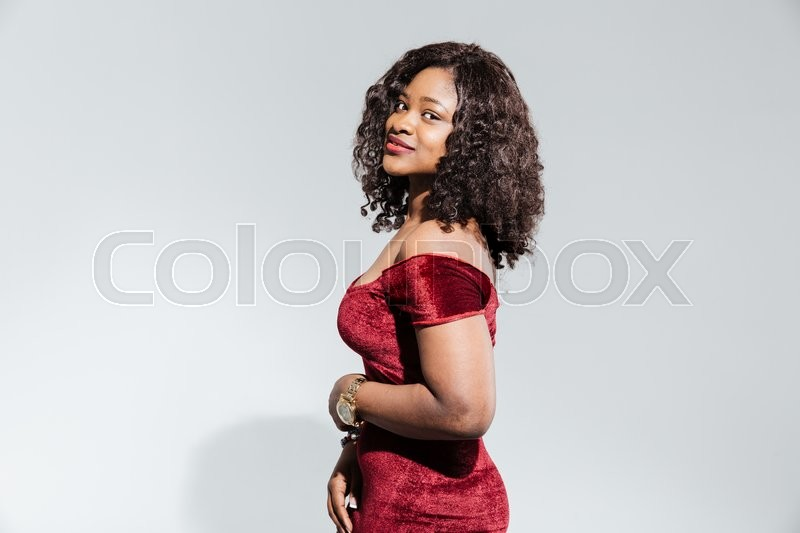 Stock image of 'Charming afro american woman in fashion dress looking at camera isolated on a white background'