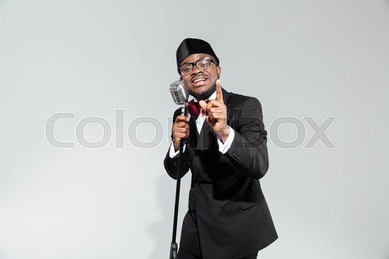 Stock image of 'Fashion afro amerian man singing into vintage microphone isolated on a white background'