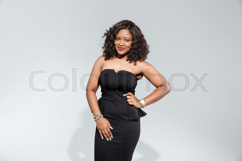 Stock image of 'Happy afro american woman in fashion dress posing isolated on a white background'