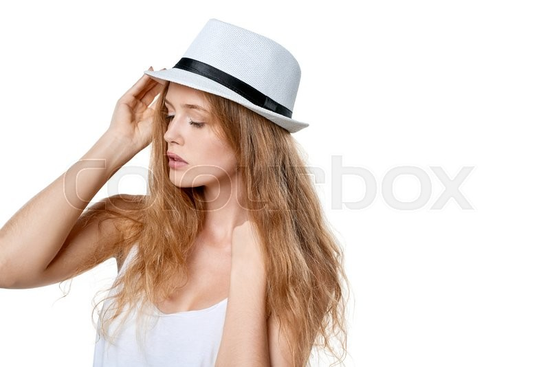 Stock image of 'Closeup of beautiful slytish woman posing in fedora hat looking away over white background'