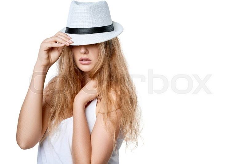 Stock image of 'Closeup of beautiful slytish woman posing in fedora hat covering eyes, over white background'