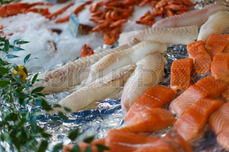 Stock image of 'Fish fillets of salmon on ice on the counter'
