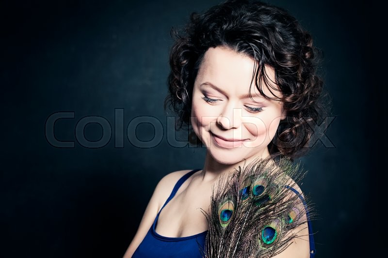 Stock image of 'Fashion Mature Woman with Makeup and Peacock Feathers'