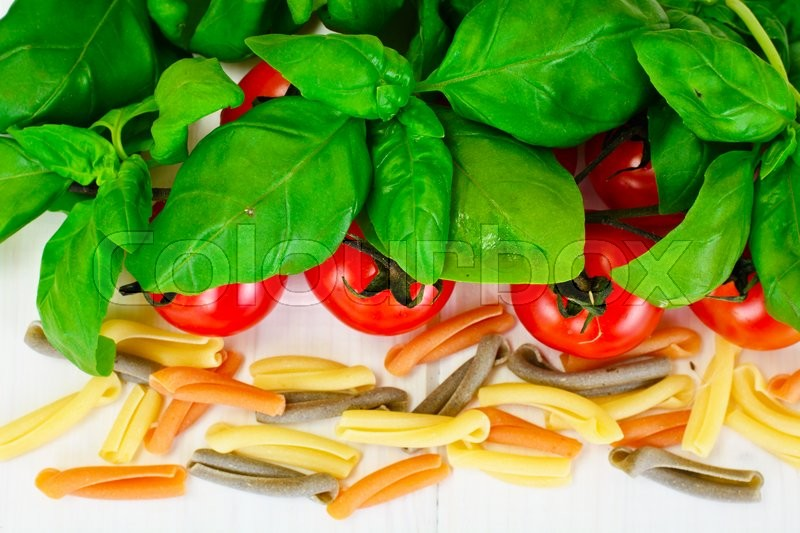 Stock image of 'Basil, Red Cherry Tomato with Pasta on White Woody Background Studio Photo'
