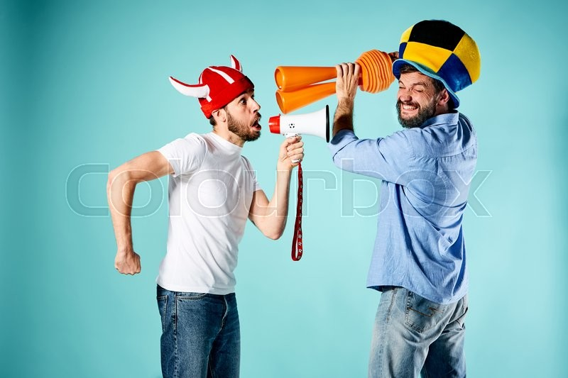 Stock image of 'The two football fans with mouthpiece over blue background'