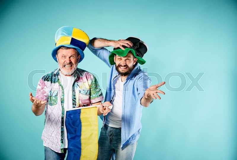 Stock image of 'The two football fans with a flag of Ukraine over blue background'