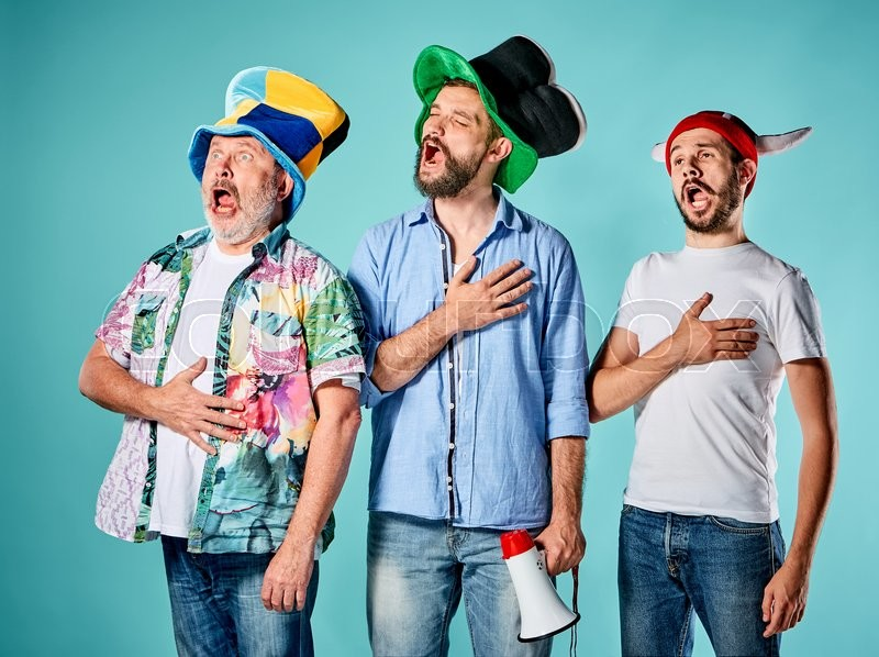 Stock image of 'The three football fans singing the national anthem over blue background'