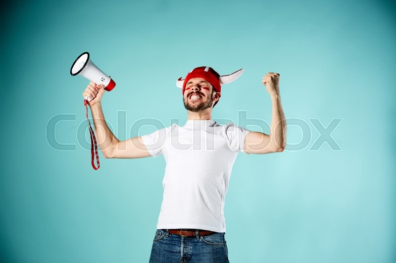 Stock image of 'The football fan with mouthpiece over blue background'