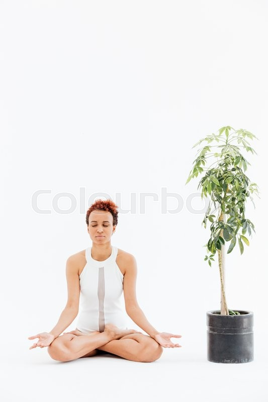 Stock image of 'Pretty african american young woman meditating and practicing yoga'