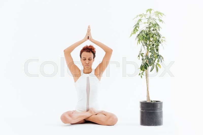 Stock image of 'African young woman sitting in lotus pose and practicing yoga'