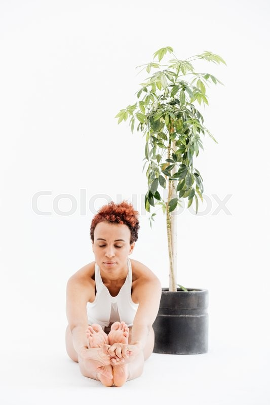 Stock image of 'African woman sitting near tree in pot and doing yoga'
