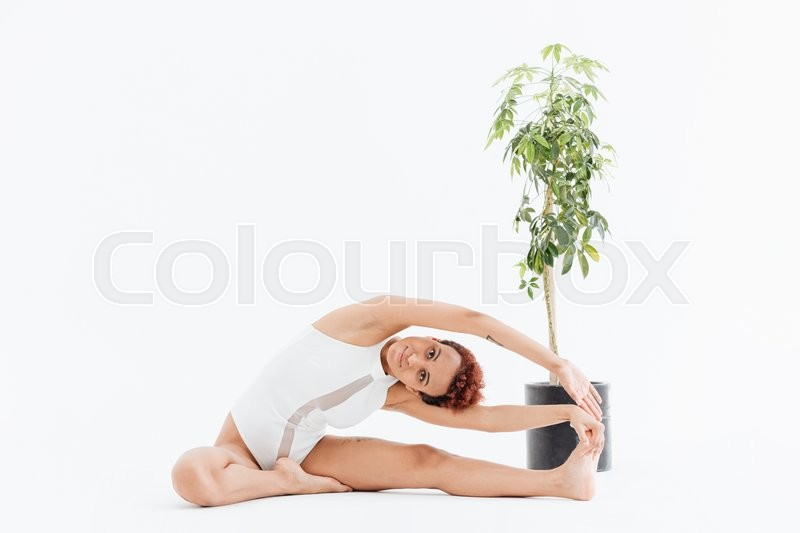 Stock image of 'Attractive african american young woman stretching and exercising yoga'
