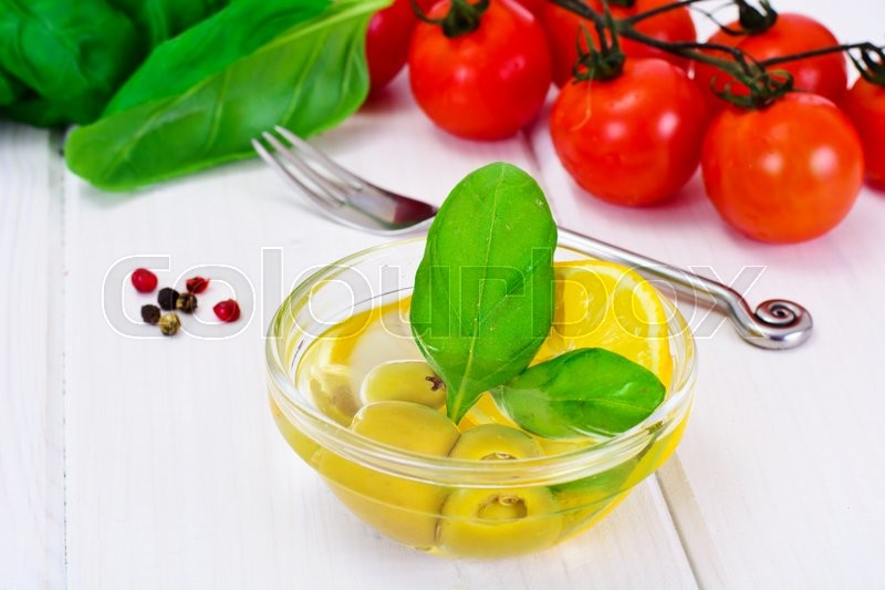 Stock image of 'Green Olives with Oil and Basil Studio Photo'