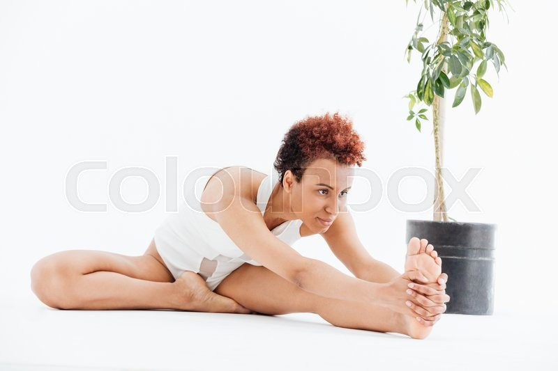 Stock image of 'Curly african american young woman stretching and doing yoga exercises'