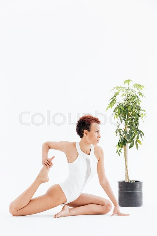 Stock image of 'Attractive african american woman doing stretching exercises and practicing yoga'