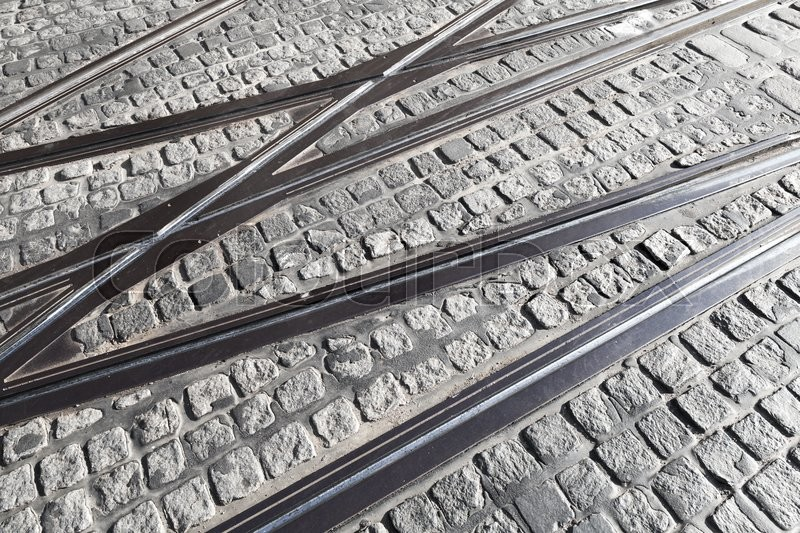 Stock image of 'Intersection of tram rails on gray stone pavement'