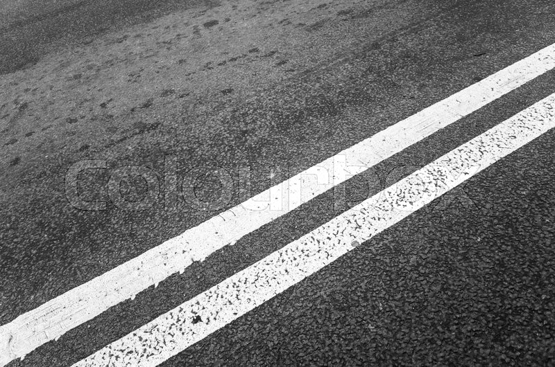 Stock image of 'White double dividing line over black highway asphalt, closeup photo with selective focus'