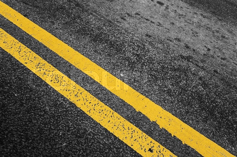 Stock image of 'Yellow double dividing line over black highway asphalt, closeup photo with selective focus'