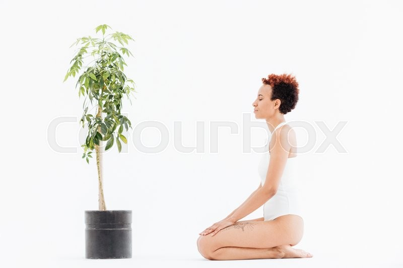 Stock image of 'Calm woman with eyes closed sitting near tree in pot'