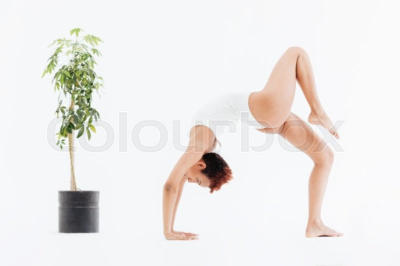 Stock image of 'Attractive african american flexible woman doing backbend yoga pose'